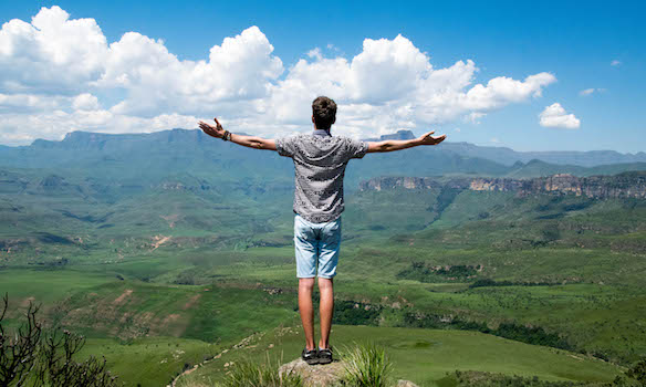 man standing at the edge of a mountain top with arms wide open